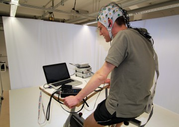 Reporter mit EEG-Kappe auf einem Fahrradergometer (Bild: Rooch)