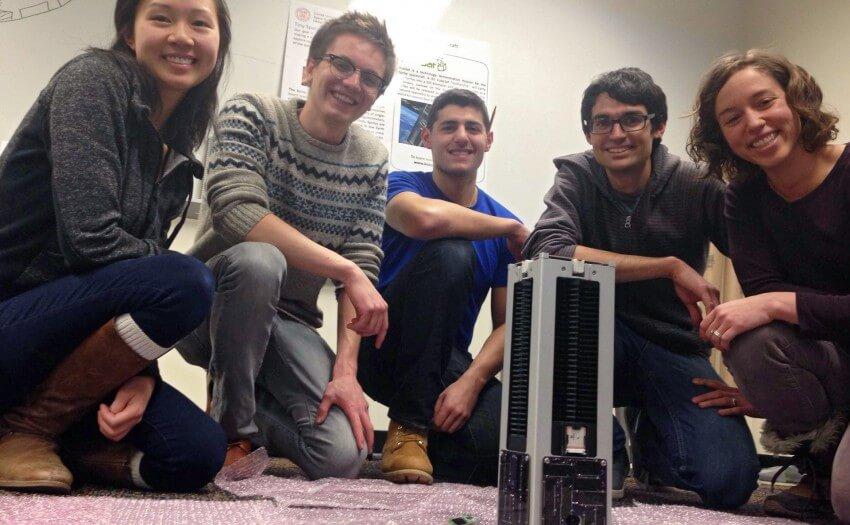 Junge Wissenschaftler knien um einen KickSat-Container (Bild: Zac Manchester/KickSat)